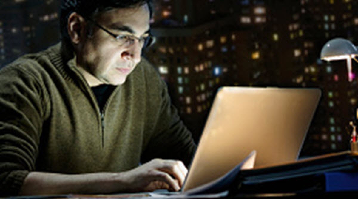 Picture of person working at a laptop at night